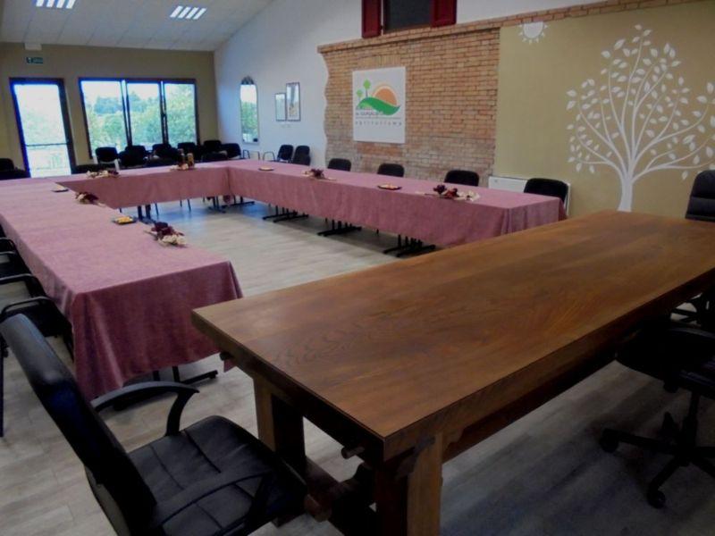Meeting aziendale di 15 persone con tavoli di appoggio, in regolare distanziamento