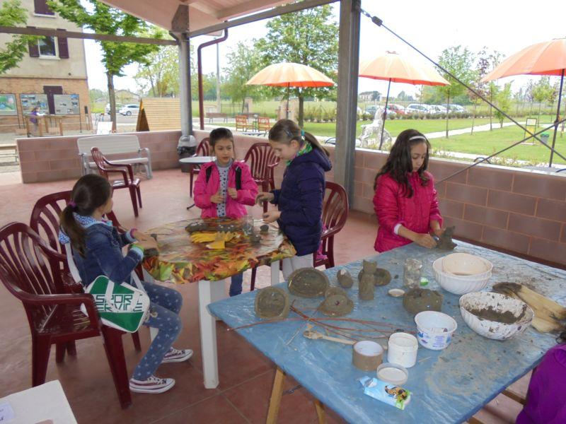 I bambini, sotto la guida di Alessandra, al lavoro per costruire oggetti con impasto di terra cruda
